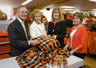 Photo of OSU Pres. Burns Hargis, First Lady and two OSU fans with plaid tartan.