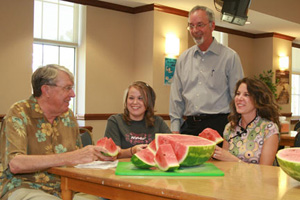 Photo of USAO president and students eating watermelon