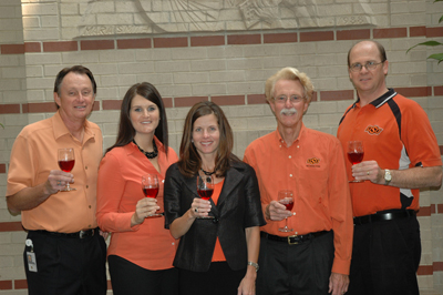 Photo of Steven Jacoby, Blair Robbins, Tina Parkhill, Ken Smith and R.D. Bell, preparing for wine tasting at OSU-Tulsa.
